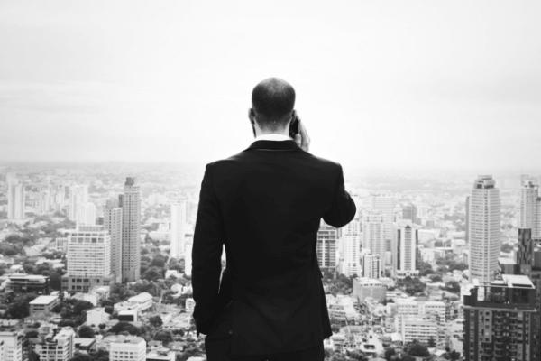 Agente de Investimentos com o telefone observa tranquilamente a cidade no horizonte