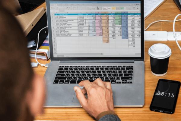 Agente de Investimentos utilizando planilha financeira em um macbook