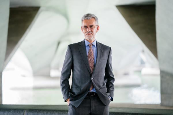 Agente de Investimentos sênior posa para foto com mãos nos bolsos, com terno cinza, camisa azul e gravata de padrão vermelho claro